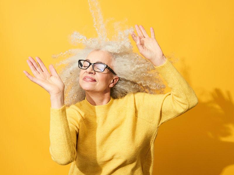 Hosszú, göndör, ősz hajú nő sárga felsőben sárga háttér előtt a karját lengeti.