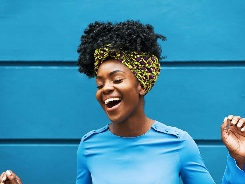 Femme aux cheveux bruns, courts et bouclés, qui porte un haut bleu et sourit sur un fond bleu.