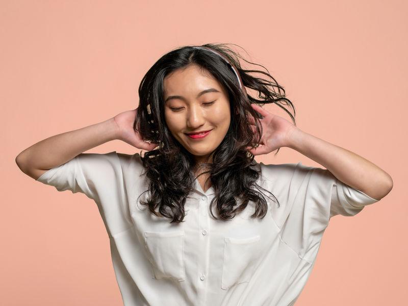 Usmiata žena vbielom tričku astmavými zvlnenými vlasmi aslúchadlami na ušiach na broskyňovom pozadí.