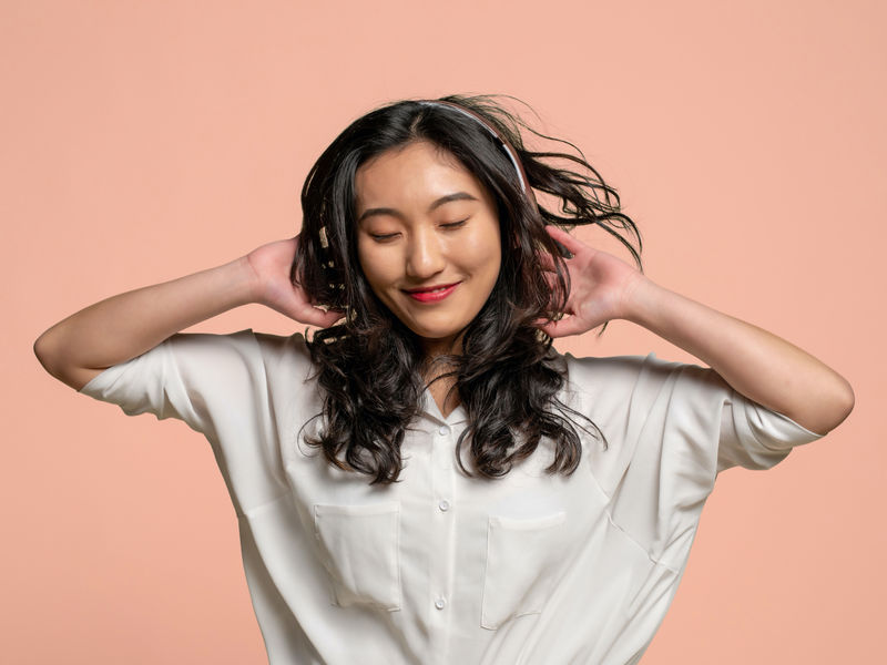 Mujer de cabello oscuro y ondulado, con una blusa blanca y auriculares, que sonríe sobre un fondo de color melocotón.