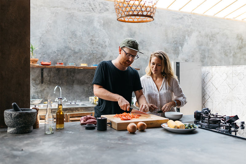 Two people – one dicing food, the other observing – in an industrial kitchen setting
