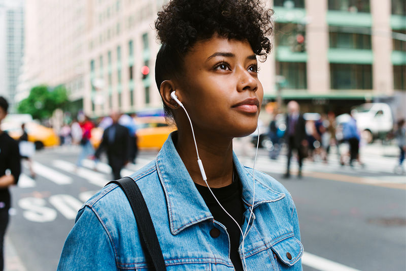 A person with short, dark, curly hair wearing a T-shirt, denim jacket and earbuds, with a buzzing city street in the background
