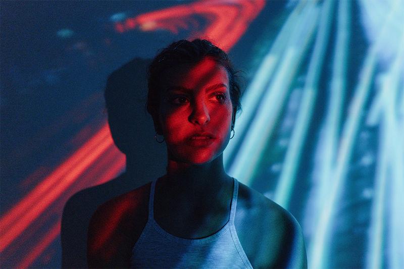 Loş bir ışık efekti yaratmak için kırmızı ve mavi çizgili bir desenin yansıtıldığı duvara karşı duran bir kişi