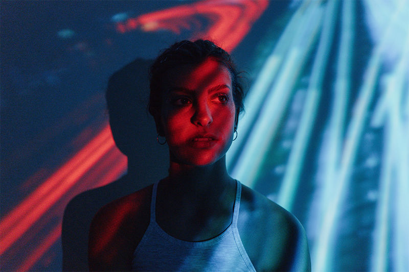 赤と青のストライプ模様でムードのある照明が投影された壁を背に人が立っている様子