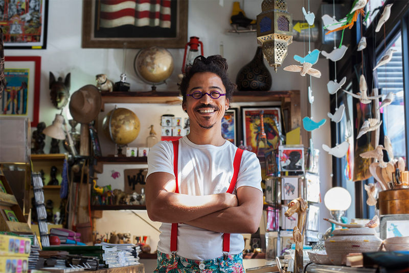 A person with dark hair in a bun and purple glasses smiling in front of a colourful, eclectic assortment of shop goods
