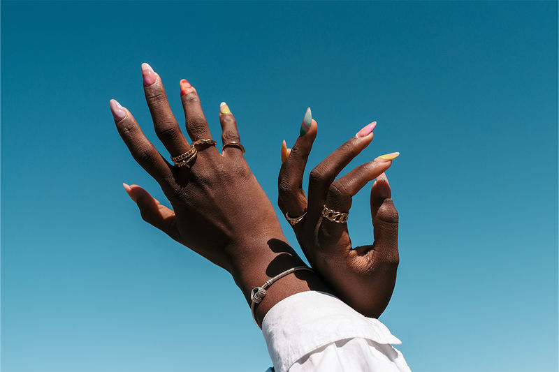 A person's hands with colourful, patterned nails and gold and silver jewellery stretched towards a blue sky